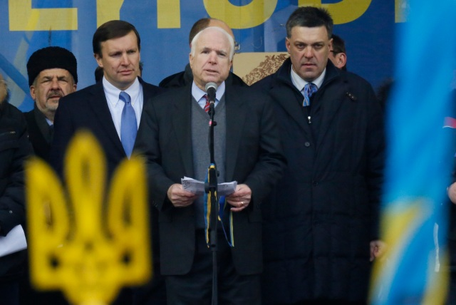 U.S. Senator John McCain, center, Democratic senator Chris Murphy, second left, Sovoboda leader Oleh Tyahnybok, right, stand around him during a Pro-European Union rally in Independence Square in Kiev, Ukraine, Sunday, Dec. 15, 2013