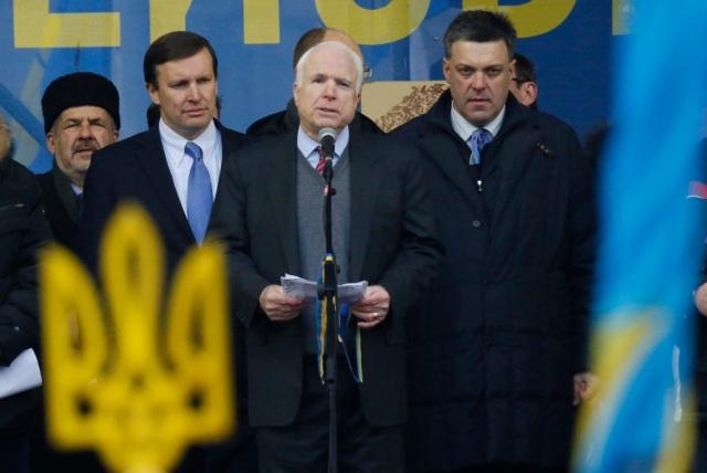 U.S. Senator John McCain, center, Democratic senator Chris Murphy, second left, Sovoboda leader Oleh Tyahnybok, right, stand around him during a Pro-European Union rally in Independence Square in Kiev, Ukraine, Sunday, Dec. 15, 2013